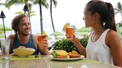 Couple dating having fun drinking alcohol on beach Stock Footage