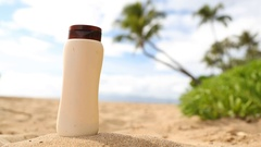 Blank sunscreen sun lotion bottle lying in golden sand on hawaii beach vacation Stock Footage