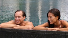 Honeymoon couple relaxing together - swimming pool Stock Footage