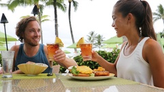Couple on summer vacation toasting mai tai drinks Stock Footage