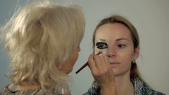 Close-up of of a beautiful young woman with esthetician making makeup Stock Footage