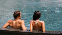 Couple in swimming-pool relaxing at hotel resort vacation travel Stock Footage