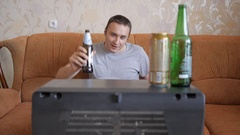 A man drinks beer and watches football on the old TV. Stock Footage