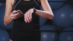 Woman with heart-rate watch and smartphone in gym Stock Footage