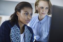 Focused businesswomen working at computer Stock Photos