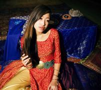 Young pretty asian girl in bright colored fairy salon interior on carpet Stock Photos