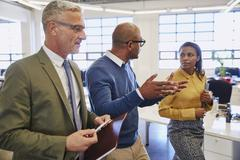 Business people walking and talking in office Stock Photos