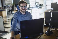 Portrait smiling businessman working at computer in office Stock Photos