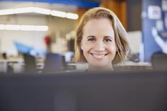 Portrait smiling businesswoman working at computer Stock Photos