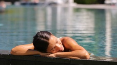 Asian woman relaxing sunbathing - pool spa health retreat body care Stock Footage