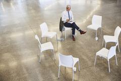 Businessman with digital tablet waiting for circle meeting Stock Photos