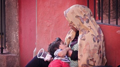 A woman breastfeeds her baby while begging in the street. Stock Footage