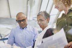 Business people discussing paperwork in meeting Stock Photos