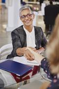 Businesswomen handshaking in meeting Stock Photos