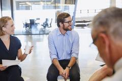 Business people smiling and listening in meeting Stock Photos