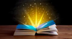 Yellow lights and sparkles coming from an open book Kuvituskuvat
