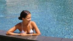 Happy woman enjoying swimming pool resort vacation Stock Footage