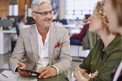 Business people with digital tablet talking in meeting Stock Photos