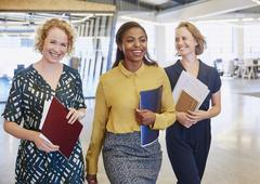 Smiling businesswomen walking in office Stock Photos