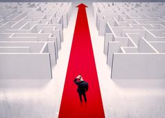 An adult elegant businessman standing on a red carpet arrow pointing ahead throu Stock Photos