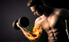 Bodybuilder athlete lifting weight with fire explode arm concept on background Stock Photos