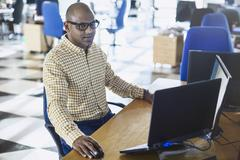 Businessman working at laptop and computer in office Stock Photos