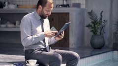 Businessman working with smartphone and tablet by pool in outdoor villa Stock Footage