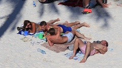 Girls and boys sunbathe on beach before Full Moon party, Koh Phangan, Thailand Stock Footage