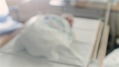 Blur to Focus on Cute Newborn Baby in Hospital Delivery Room Bed Stock Footage