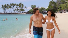 Sexy suntan interracial couple walking on beach during summer vacation holiday Stock Footage