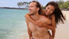 Attractive happy couple laughing having fun piggybacking on tropical beach Stock Footage