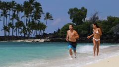 Happy couple having fun together running on beach playful and joyful Stock Footage