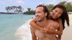 Attractive happy couple laughing having beach fun on tropical beach Stock Footage