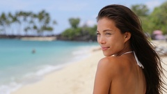 Beautiful Asian bikini woman relaxing on beach blowing a kiss at camera Stock Footage