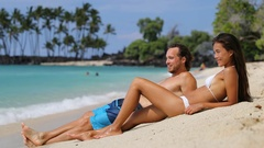 Couple relaxing on suntan beach vacation holiday - Happy young adults sunbathing Stock Footage