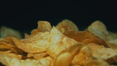 Potato Chips Rotating On Black Background in Slow Motion Stock Footage
