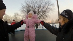 Grandparents playing with a little girl on a trampoline in the winter park Stock Footage