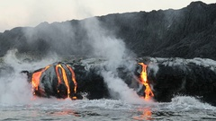 Lava flowing into the ocean from volcano lava eruption on Big Island Hawaii Stock Footage