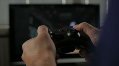 Man playing a video game using a game controller. With TV. Console Video Game. Stock Footage