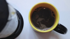 Pouring coffee into a mug with smiley face at the bottom. Reverse speed. Stock Footage