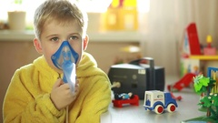 the boy is breathing through a nebulizer mask Stock Footage