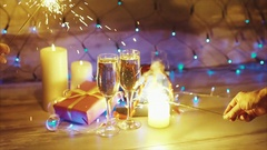 Hands with sparklers on the background of Christmas gifts candles and champagne Stock Footage