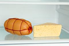Fresh appetizing sausage and cheese on refrigerator shelf. Stock Photos