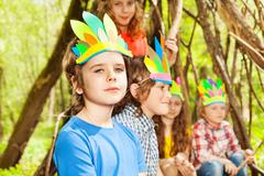 Cute boy in Injun's headdress playing with friends Stock Photos