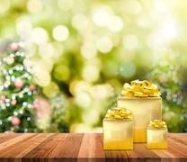 Golden presents on wood plank table top with christmas bokeh light Stock Photos