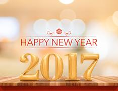 Happy new year 2017 on wood plank table top with blur abstract bokeh background Stock Photos