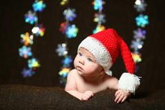Christmas baby with a red and white bombon christmas hat looking aside Stock Photos