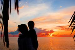 Silhouette of father and daughter on the beach at dusk Stock Photos