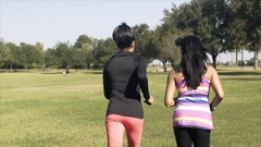 Slow motion following two young women jogging in a park Stock Footage