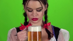 Girl blowing in glasses with beer bites his lip. Slow motion Stock Footage